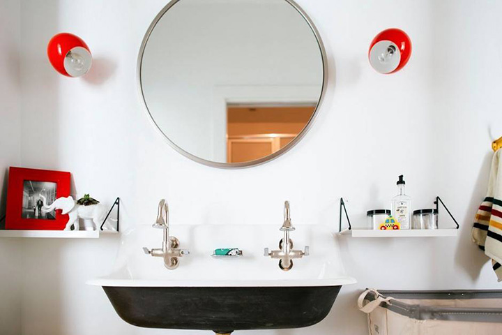 Bright bathroom with industrial fixtures, colorful accents, and chic accessories