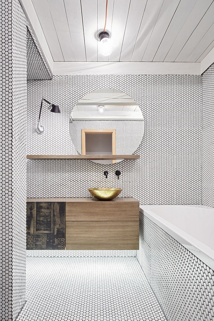 Contemporary style bathroom with bathtub, tiny mosaic tiles, gold sink, and dramatic wooden vanity