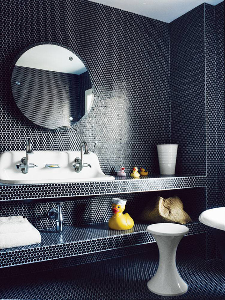 Kid friendly dark blue mosaic tile bathroom with huge rubber ducky and plastic cup, including double sink and round mirror