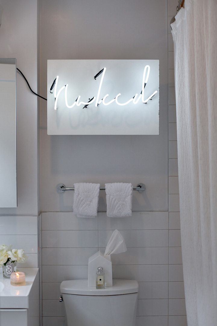 "All white bathroom with neon ""Naked"" sign, candles, and glamorous vibe"
