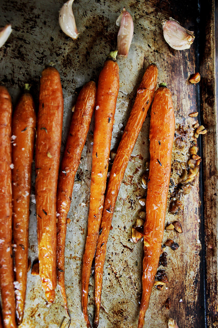 Roasted carrots on baking sheet with garlic cloves
